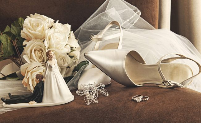 Bouquet of white roses and wedding shoes on chair